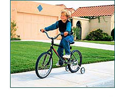 Child with training wheels, riding bike
