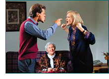 Husband and wife arguing with old lady smiling on