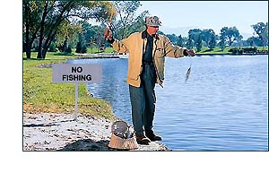 Man fishing next to 'no fishing' sign